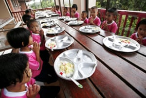 Young students give thanks for their lunch