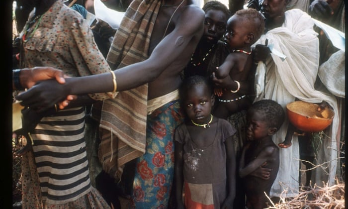 Famine victims wait in line for food distribution at a World Vision feeding center June 15, 1998 in Thiet, Sudan. Following fifteen years of civil war and two years of intense drought an estimated 700,000 Sudanese are at risk of starvation and sixty to seventy die each day in the hardest hit areas like Bahr-al-Ghazal. (Photo by Malcolm Linton/Liaison)AfricaBahralGhazalfaminefeedingcenterhalflengthreliefagencyskeletalstarvationSudanThietvictimWorldVision
