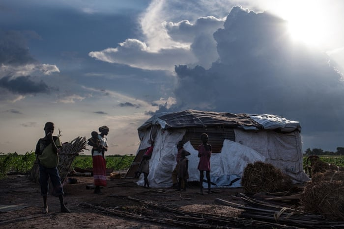 Martha Nyarueni (2ndL) and her family stand outside their home outside the town of Leer, South Sudan, after receiving aid package, on July 5, 2014.