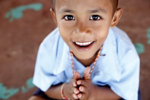 Seven-year-old Cafae holds a neck amulet, a gift from his father, as he prepares for morning meditation