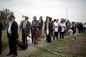 Delegates, observers and journalists stand in line for transportation to the Climate Change Conference facilities in Lima, Peru, Monday, Dec. 1, 2014. Delegates from more than 190 countries will meet in Lima for two weeks to work on drafts for a global climate deal that is supposed to be adopted next year in Paris.