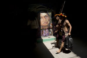 Indians walk though a tunnel decorated with several murals during the Climate Change Conference in Lima, Peru, Monday, Dec. 1, 2014. Delegates from more than 190 countries will meet in Lima for two weeks to work on drafts for a global climate deal that is supposed to be adopted next year in Paris.