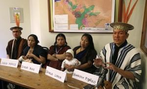 Brazil's Ashaninka indigenous leader Francisco Piyako, right, speaks during a press conference with the widows and daughters of two indigenous leaders who were allegedly slain by illegal loggers, during the Climate Change Conference in Lima, Peru, Wednesday, Dec. 3, 2014. Second from right is Ergilia Rengifo holding her baby and sitting next to her daughter Diana Rios. Second from left is Julia Perez breastfeeding her baby. At far left sits Ashaninka indigenous leader Isaac Pikayo. Perez' husband was anti-logging activist Edwin Chota, and Rengifo's husband was Ashaninka leader Jorge Rios Perez. Both were killed in Sept. 2014 and several illegal loggers have been arrested as suspects in the killings. The widows and leaders asked for justice, the halt of logging and titles to their ancestral land.