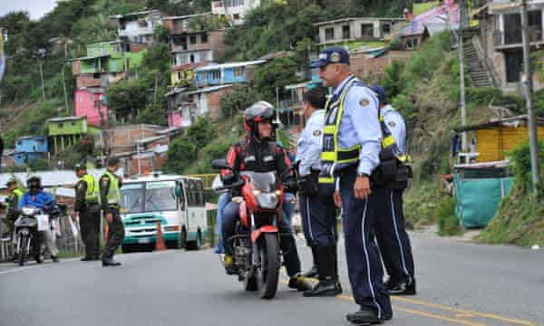 Police officers stop traffic in the shantytown of Terron Colorado in Cali, Colombia