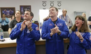 Nasa astronauts cheer as they watch the landing of the Orion test flight on a television at the Kennedy space centre.