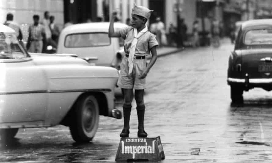 A primary school boy assists local policemen in directing traffic in San José, Costa Rica.