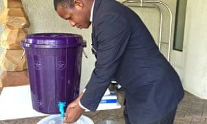 Man washing at tap in Sierra Leone