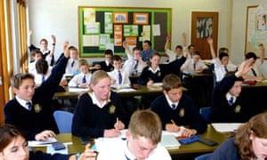 children raise their hands in a classroom