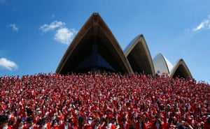 Thousands of runners pose for a group photo after completing an annual Santa fun run from Darling Harbour to the Sydney Opera House, Australia