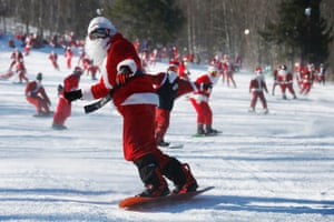 Skiers and snowboarders participate in a charity run down a slope at Sunday River Ski Resort in Newry, Maine