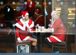 Competitors dressed in Santa costumes look out from a coffee shop before a fun run in Loughborough