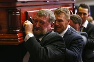 Gregory Hughes carries the coffin of his son Phillip Hughes during the funeral service at Macksville High School Stadium