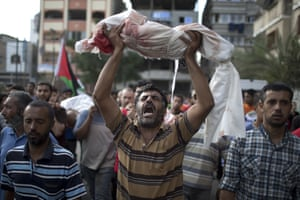 A Palestinian man holds up the body of one-year-old baby Noha Mesleh, who died of wounds sustained after a UN school in Beit Hanun was hit by an Israeli tank shell, during her funeral in Beit Lahia, northern Gaza Strip, on 25 July.