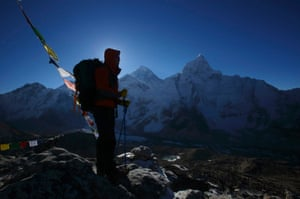 A trekker stands in front of Mount Everest, which is 8,850 meters high, at Kala Patthar in Solukhumbu district 7 May. In April, an avalanche killed 16 Nepali Sherpa guides who were fixing ropes and ferrying supplies for their foreign clients and the accident - the deadliest in the history of Mount Everest - triggered a dispute between sherpa guides who wanted a climbing ban in honour of their colleagues and the Nepali government that refused to close the mountain