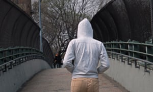 Back of teenage girl in hoodie on pedestrian bridge