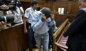 Zola Tongo (C), covers his face as policemen escort him to the Cape Town high court, in December 2010.