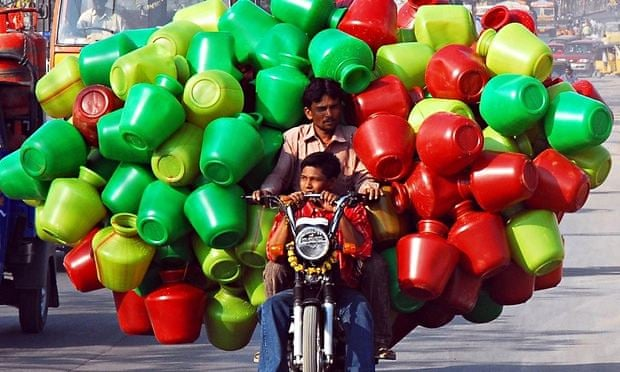 Motorbike rider with boy young passenger carrying huge number of plastic water storage pots