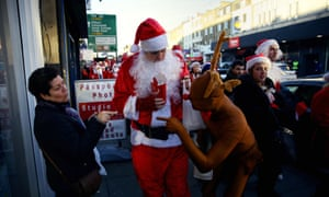 Stephen Moss on the SantaCon parade with Rudolph and a passerby