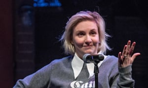 Lena Dunham in sweatshirt with smirk on her face and hand raised