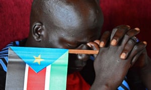 A man holds a South sudan flag at an anniversary celebration of the Red Army Foundation in Juba.