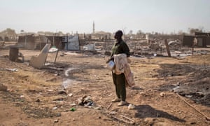 A man carrying his belongings stands amongst the remains of buildings destroyed by the recent fighting in the provincial capital of Bentiu, in Unity State, South Sudan.