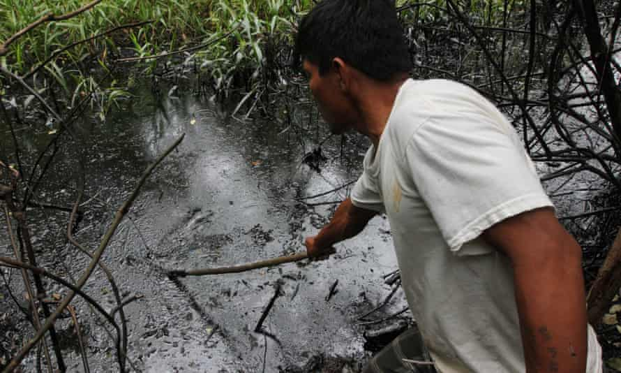 A Kukama Indian check oil following oil spill due to broken pipeline in Amazonian forest of Peru that polluted the Marañón River, a major tributary of the Amazon, June 2014.