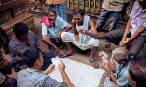 Men play a game of cards amid the bustle of the city. Kolkata, India