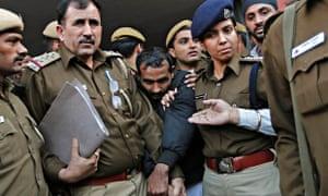 Policemen escort driver Shiv Kumar Yadav outside a court in Delhi.