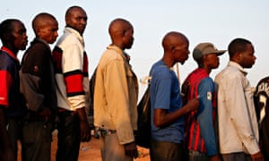 Bus passengers wait to be searched for weapons by Kenyan police in the town of Mandera