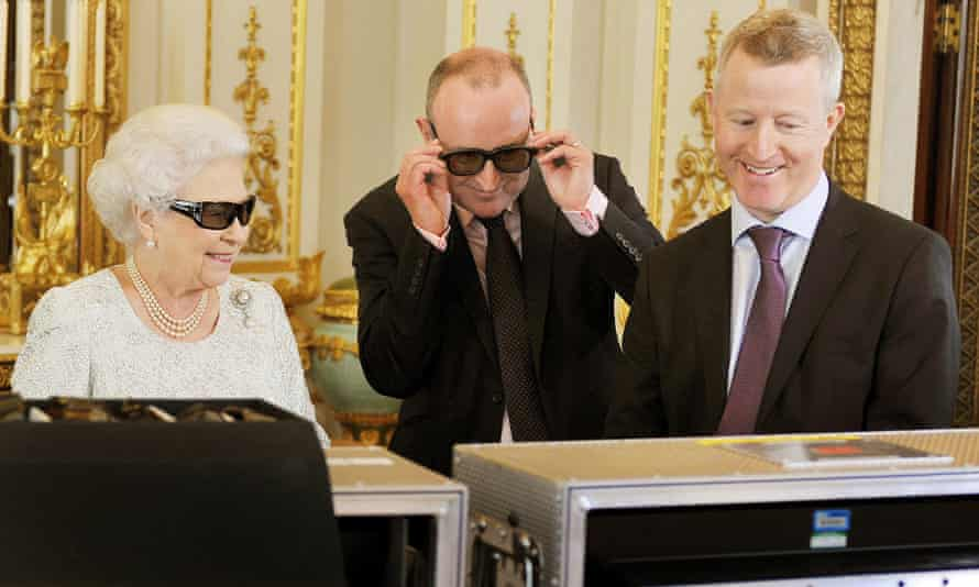The Queen dons 3D glasses to view footage of her 2012 message with producer John McAndrew (centre) and director John Bennett.