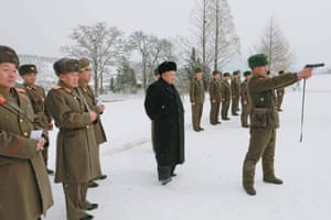 North Korean leader Kim Jong Un (C) stands in the snow as he inspects KPA Unit 1313 honored with the title of O Jung Hup-led 7th Regiment in Pyongyang