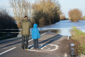 A man and his child look out onto the A361 in Somerset which is closed due to flooding. East Lyng has virtually been cut off with only one route in and out of the village.