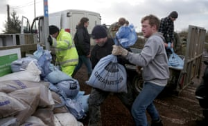 Volunteers moves sandbags to help stabilise a pathway at  Burrowbridge on the Somerset Levels near Bridgwater, England.