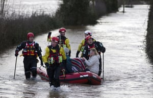 Devon and Somerset Fire and rescue service evacuate two women and two cats in baskets through flood waters in Burrowbridge.