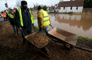 Volunteers moves chippings to help stabilise a pathway at  Burrowbridge on the Somerset Levels  near Bridgwater, England.