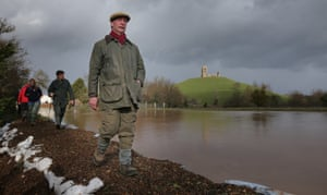 Leader of UKIP Nigel Farage walks past flood water surrounding Burrow Mump as he visits at Burrowbridge on the Somerset Levels near Bridgwater, England.