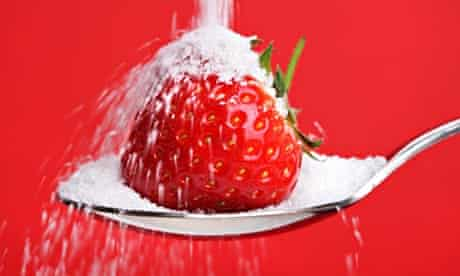 Strawberry on spoon with sugar