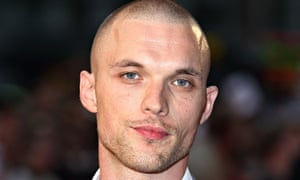 Ed Skrein with his shaven head, stubble and open-necked shirt and grey suit