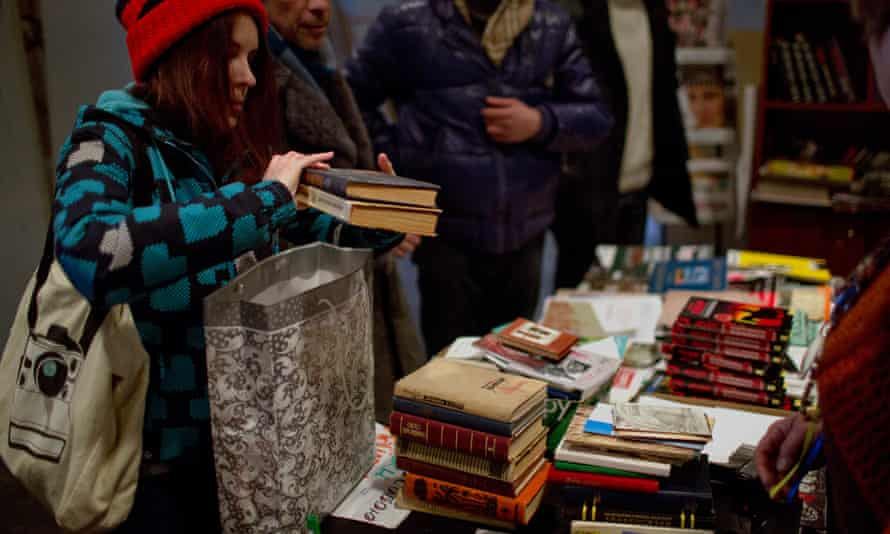 A woman delivers books to an improvised library in one of the buildings seized by demonstratiors in Kiev