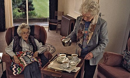 Home help serving up tea and cakes to elderly woman