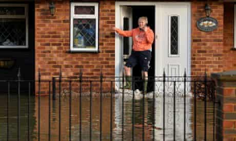 A resident stands at her front door in Wraysbury