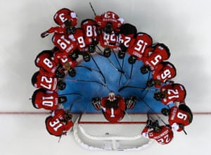 Canada's women's ice hockey team surrounds goalie Shannon Szabados before their women's ice hockey game against Finland at the 2014 Sochi Winter Olympics.