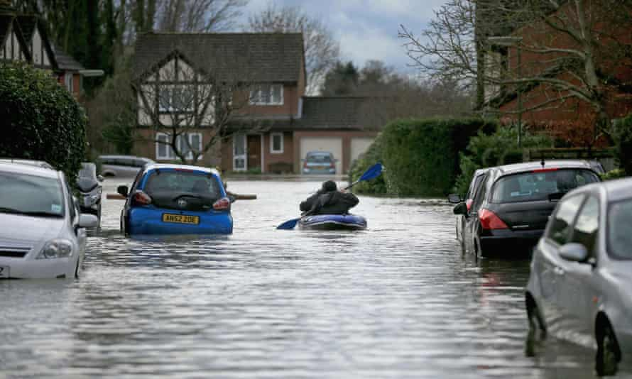 Residents use a boat make their way through floodwater that has cut off their homes on February 11, 2014 in Chertsey.