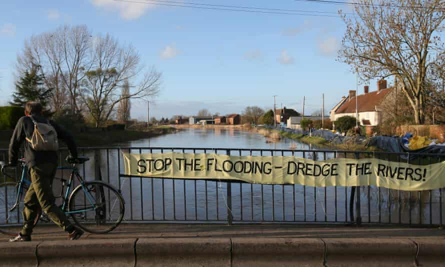 """A cyclist goes over a bridge where locals have put up a sign 'Stop the Flooding - Dredge the Rivers"""" on the River Parrett, at Barrow Mump,  in Somerset, England."""