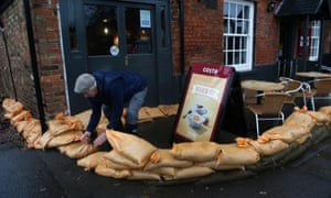 A resident moves sandbags to surround a property from the floods, in the centre of the village of Datchet, England