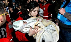A Syrian Red Crescent worker carries a baby on to a bus as 1,100 civilians are evacuated from Homs