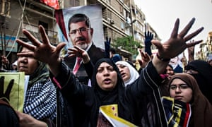 A woman stretches out her hands towards the camera in front of a poster of Morsi in street in Cairo