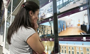 Young first time buyer looking at houses for sale in estate agent window