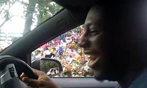 Royal Barnes laughs driving past the floral tributes in a still from  his video