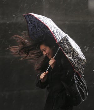 A woman struggles to keep dry in Southwark,  London.